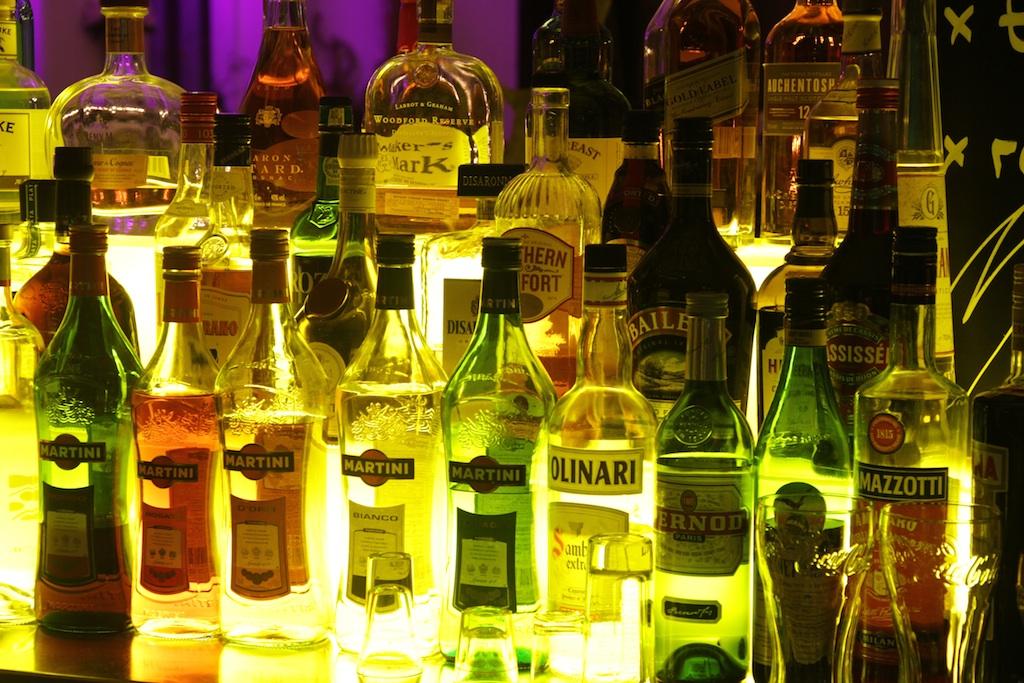 Die Bar. Farben froh leuchten die Flaschen im Licht der Bar